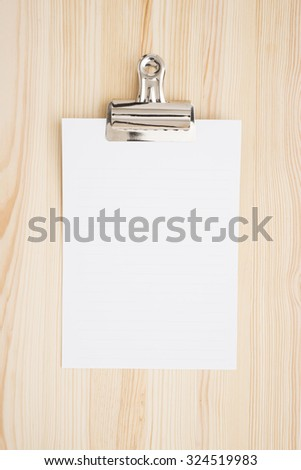 Empty white paper on wooden table in office.