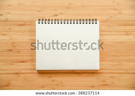empty white paper page of binder notebook on wooden texture of office table - use for background in business or education concept - stock photo
