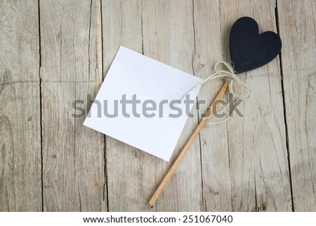 Empty white paper with heart-shaped decoration on a wooden table for any kind of notes or messages. - stock photo
