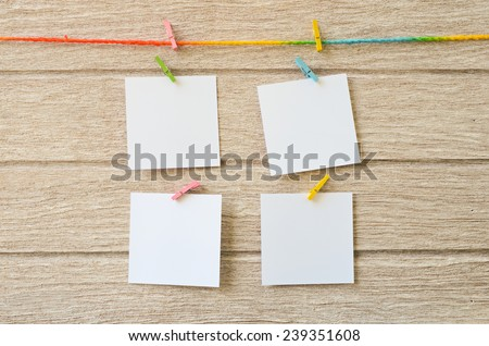 empty white photo frames hanging with clothespins on wooden background  - stock photo