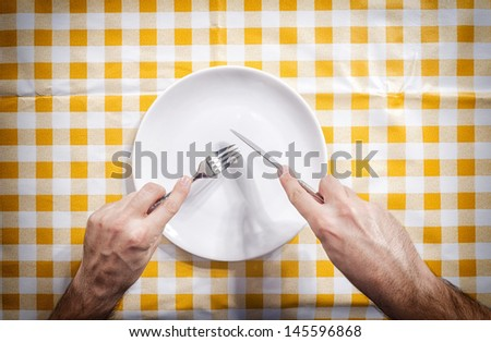 Empty white plate and human hands from above