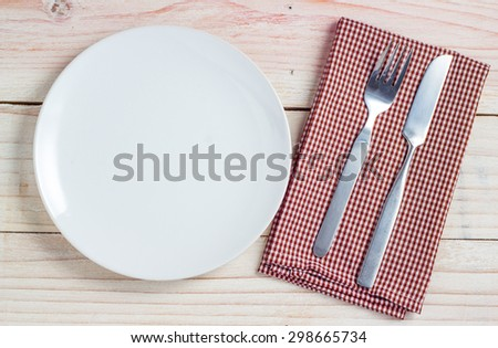 Empty white plate and silverware on white wooden table background - stock photo