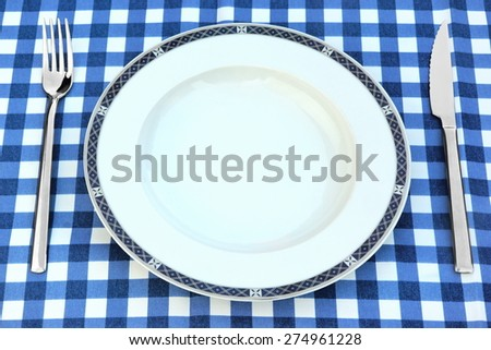 Empty White Plate, Knife And Fork On The Checkered Blue White Picnic Tablecloth Background - stock photo