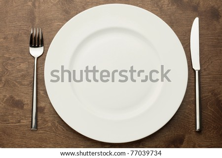 empty white plate on a wooden table with fork and knife