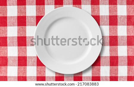 empty white plate on red checkered tablecloth