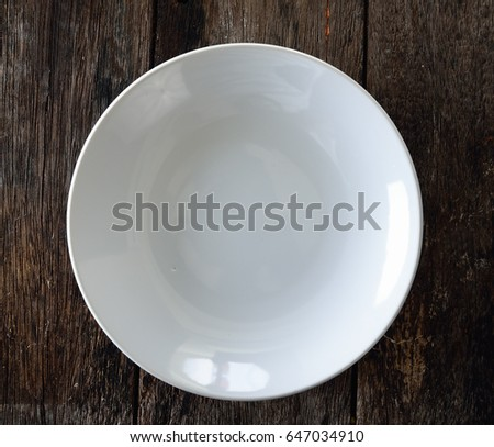 empty white plate on wooden