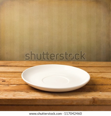 Empty white plate on wooden table over grunge striped wallpaper - stock photo