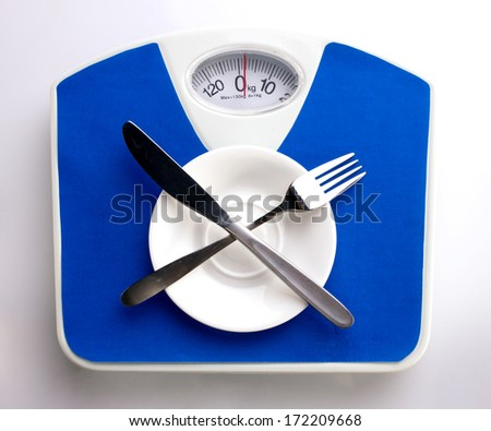 empty white plate, spoon and knife on blue scale for dieting concept  - stock photo