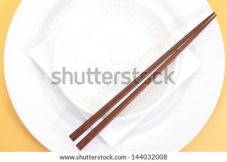 Empty white plate with chopsticks - stock photo
