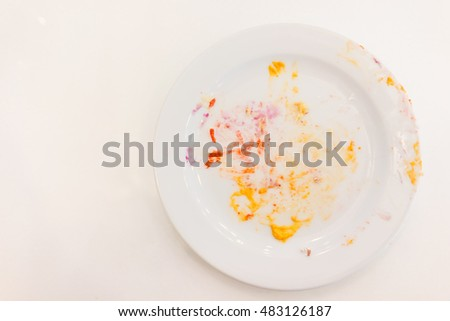 Empty white plate with crumbs and cream after eating