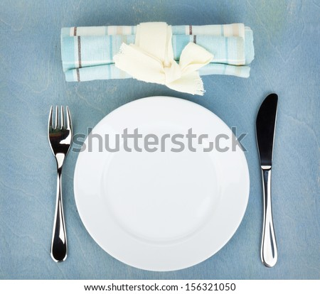 Empty white plate with silverware on blue wooden table - stock photo