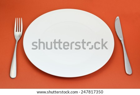 empty white porcelain plate with fork and knife set on red background - stock photo