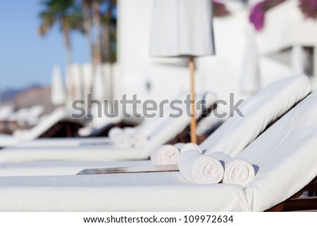 empty white sunbeds at the modern resort - stock photo
