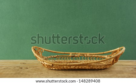 empty wicker basket on an old wooden table  against grunge wall