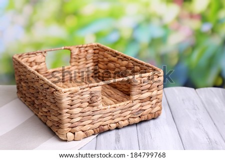 Empty wicker basket on wooden table, on bright background - stock photo