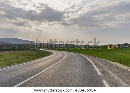 Empty winding country road against dramatic sky - stock photo