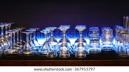 Empty wine and whisky glasses arranged on blue background in the bar