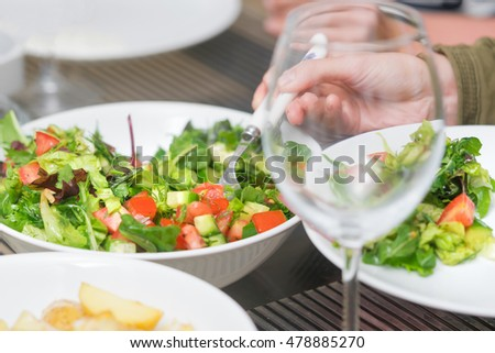 Empty wine glass, a human hand with a spoon and vegetable salad with tomatoes and greens on a white plate