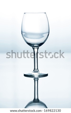 Empty wine glass on blue and white gradient background - stock photo