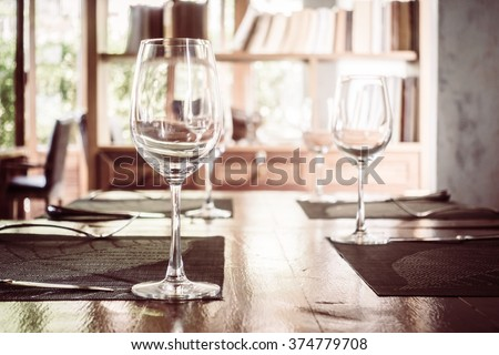 Empty wine glass on dining table in restaurant -  Vintage Filter and Selective focus point - stock photo