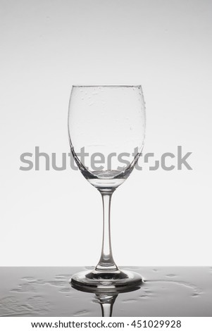 Empty wine glass on wet table in white background - stock photo