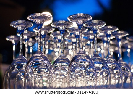 Empty wine glasses arranged in row, setup for wedding ceremony.