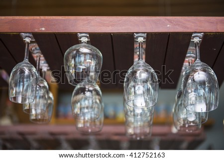 empty wine glasses hanging over the bar, row