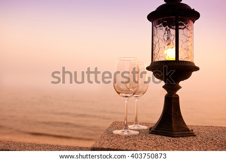 Empty wine glasses in a background of sunset sky and sea