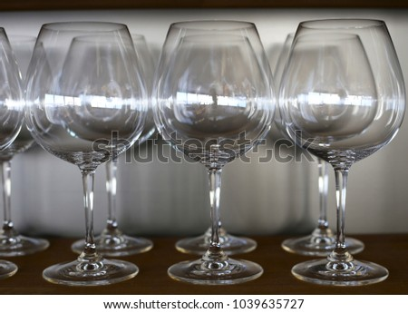 Empty wine glasses on a shelf in a bar
