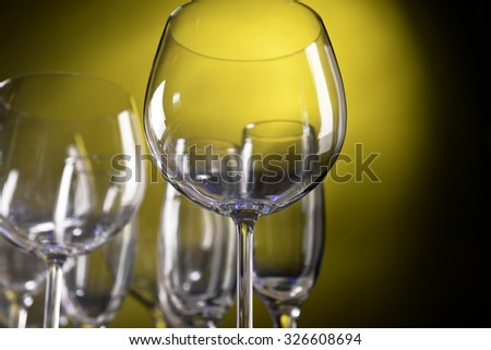 Empty wine glasses on yellow background - stock photo