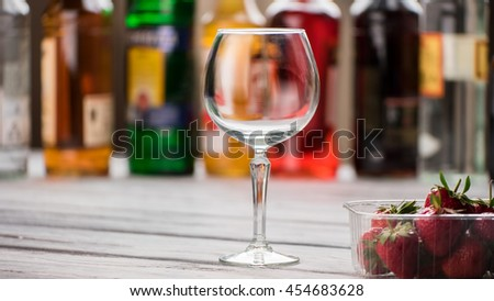Empty wineglass and strawberries. Berries in container. Wooden table at the bar. Who wants a drink. - stock photo