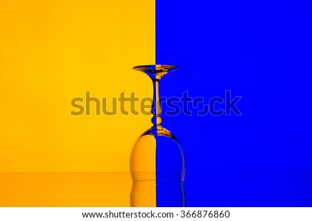 Empty wineglass on yellow and blue