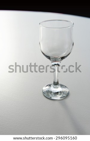 Empty wineglass stands on white round table