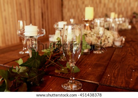 Empty wineglasses stand on the table around the flowergarland - stock photo