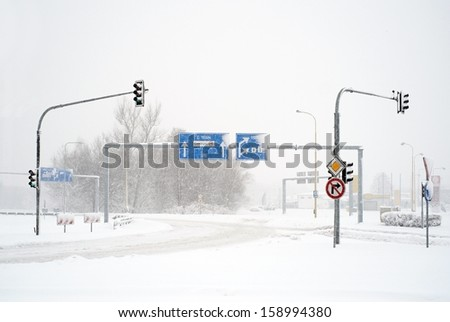 Empty winter road with traffic signs in snow storm - stock photo