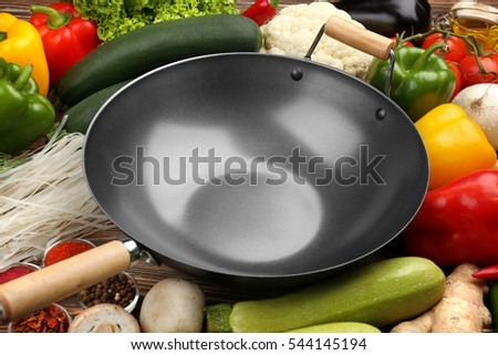Empty wok pan with vegetables, closeup