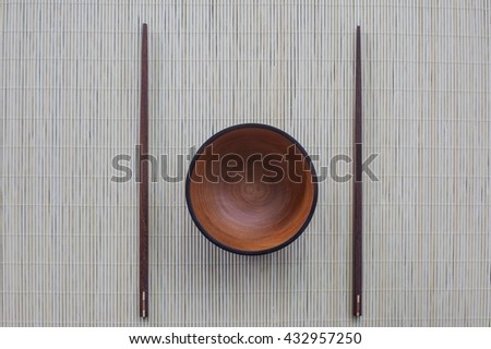 Empty wood bowl and chopsticks - stock photo