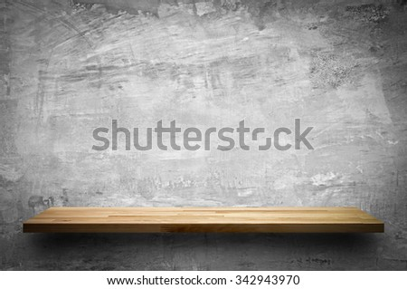 Empty wood shelf on bare concrete wall background - stock photo