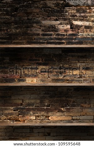 Empty wood shelf on old brick wall background, grunge industrial interior Uneven diffuse lighting version. - stock photo