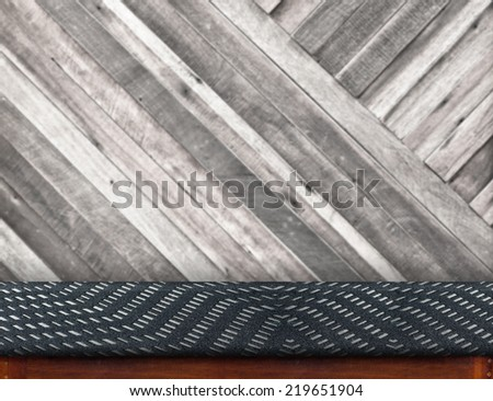 Empty wood table cover with black fabric at blurred pale plank wooden wall in  background,Template for display your product