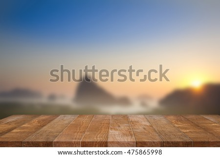 Empty wood table platform, terrace for present product on blurred sunset sky background