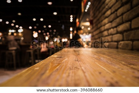 Empty Wood Table Top Of Bar With Blur Of Cafe Restaurant In Dark Night  Background/