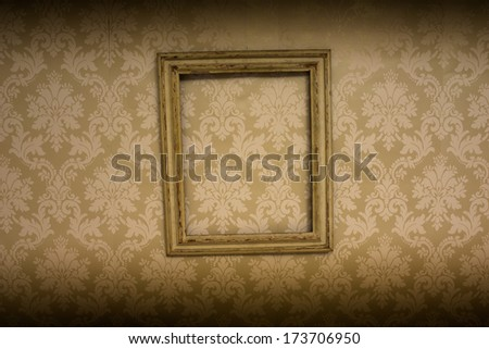 Empty wooden antique picture frame hanging on retro beige wallpaper with an arabesque pattern with vignetting on the top and bottom borders of the frame - stock photo