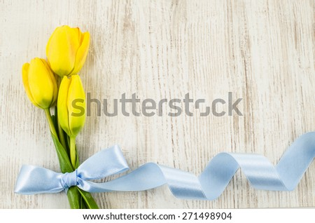 Empty wooden background with colorful flowers and blue ribbon - stock photo