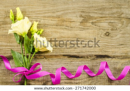 Empty wooden background with colorful flowers and pink ribbon - stock photo