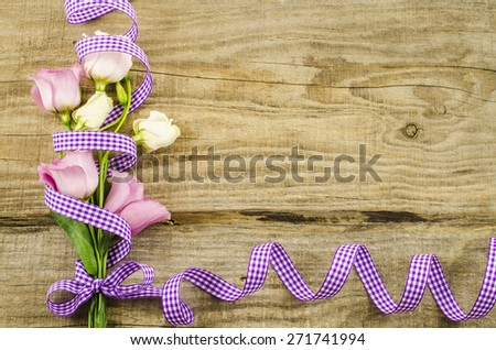 Empty wooden background with colorful flowers and purple ribbon - stock photo