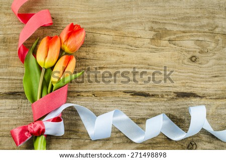 Empty wooden background with colorful flowers and ribbon - stock photo