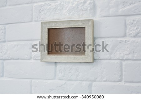 Empty wooden beige picture frame at white brick wall