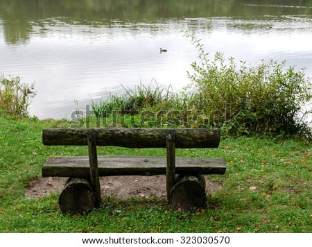Empty wooden bench near a lake