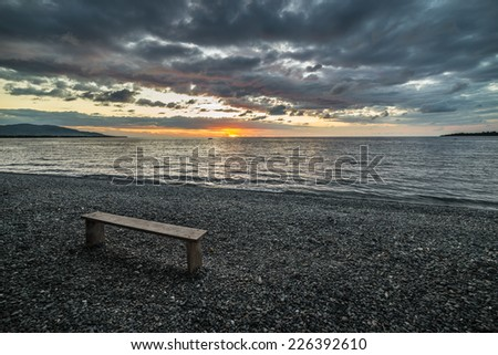 Empty wooden bench placed on pebbly beach with romantic sky at sunset on the coastline of Ampana, Central Sulawesi, Indonesia. - stock photo
